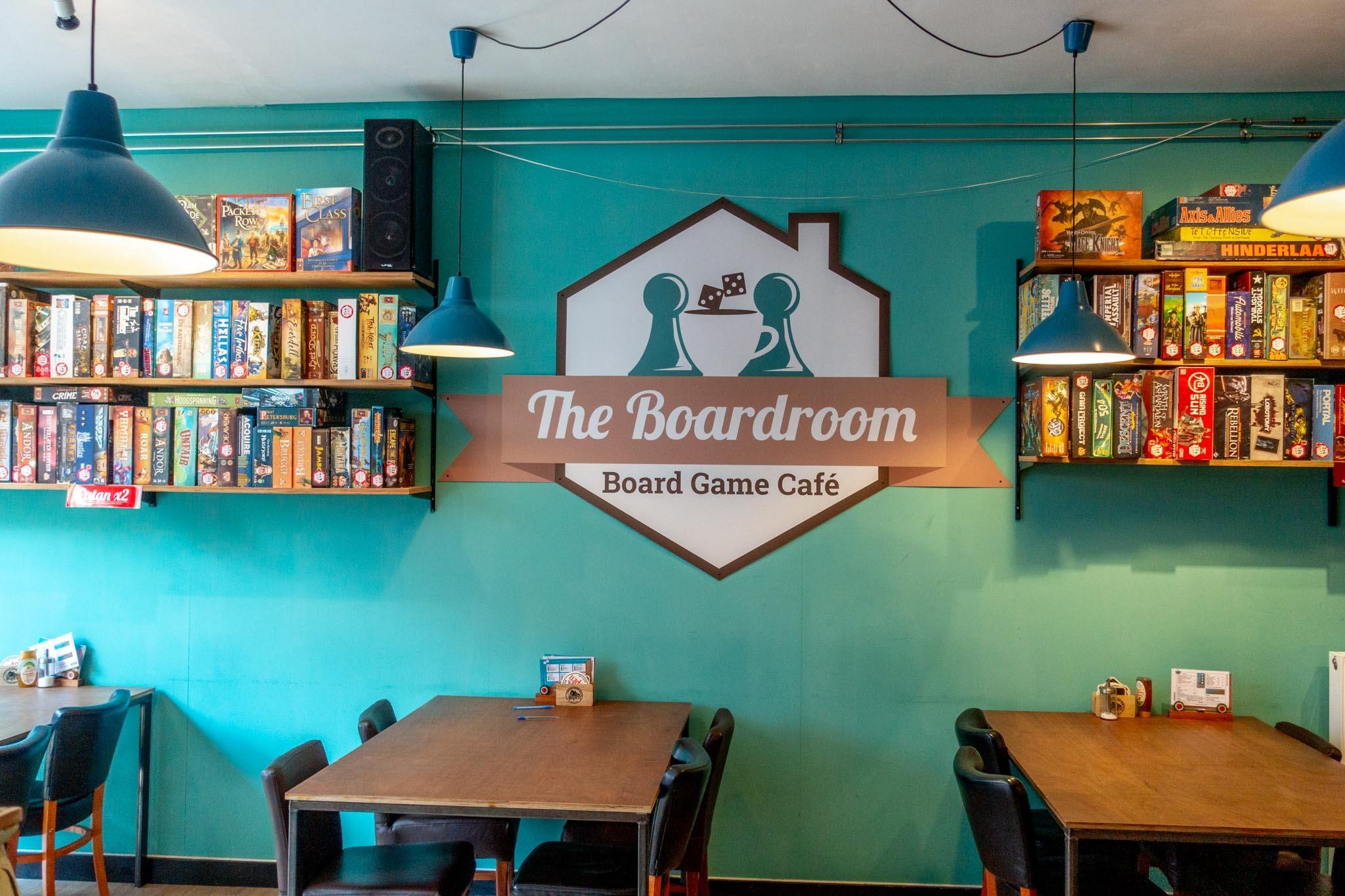 Interior of the Boardroom Cafe with tables, chairs, and boardgames on shelves on the wall