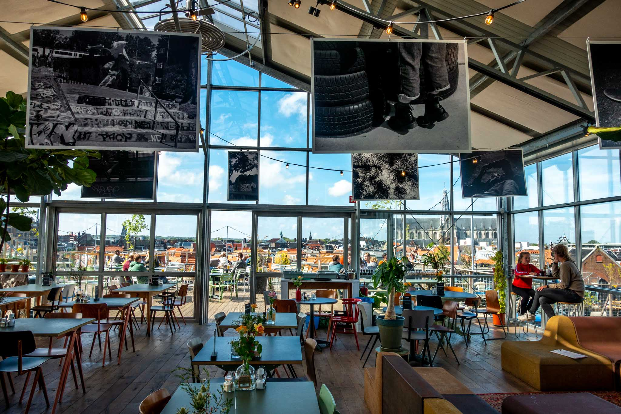 Tables inside a rooftop cafe with glass walls and a view over Haarlem