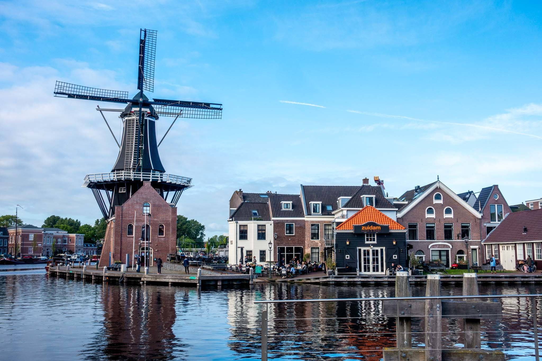 Windmill and buildings overlooking a river in Haarlem Netherlands