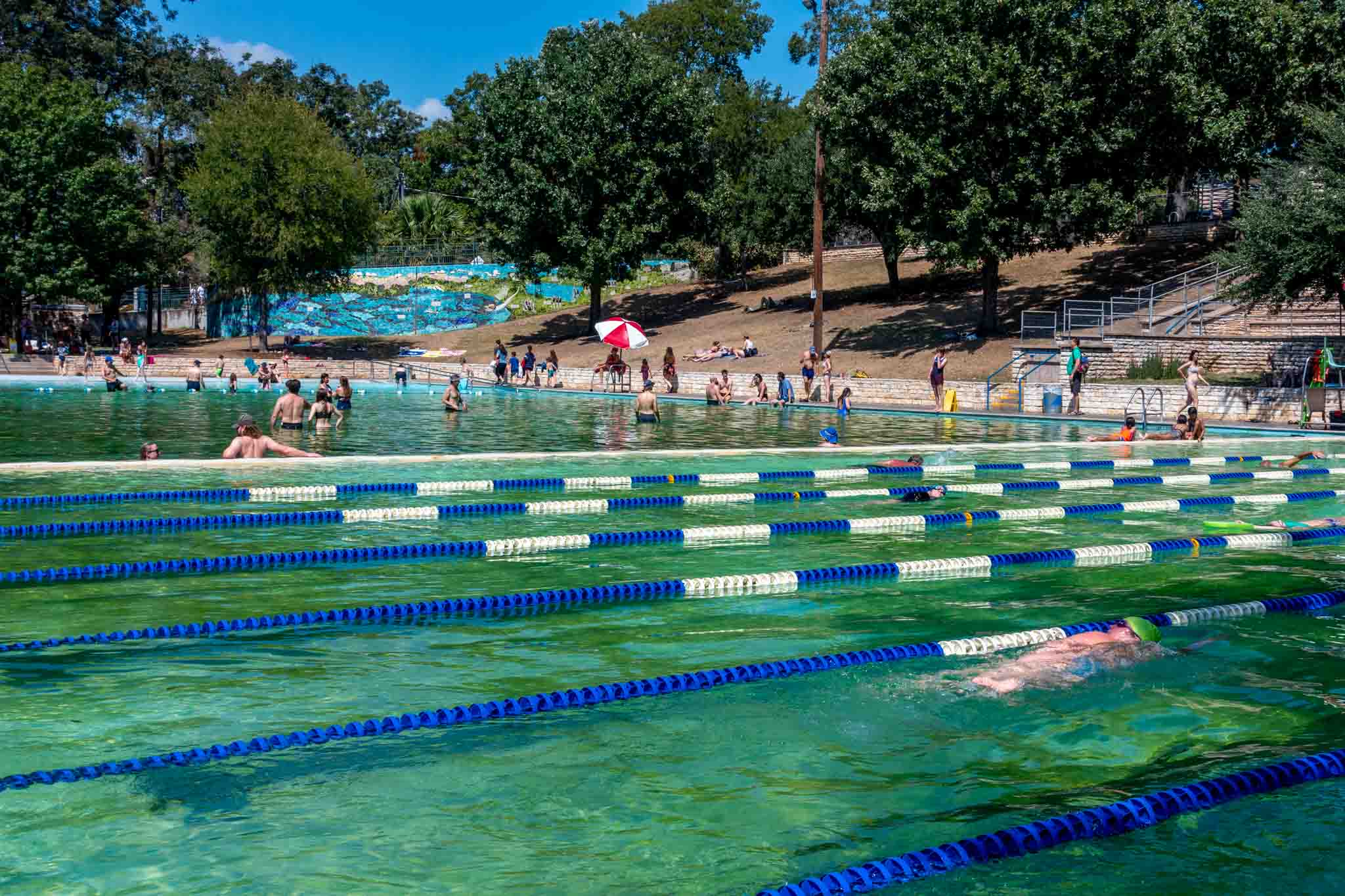 People at a large swimming pool, Deep Eddy Pool in Austin