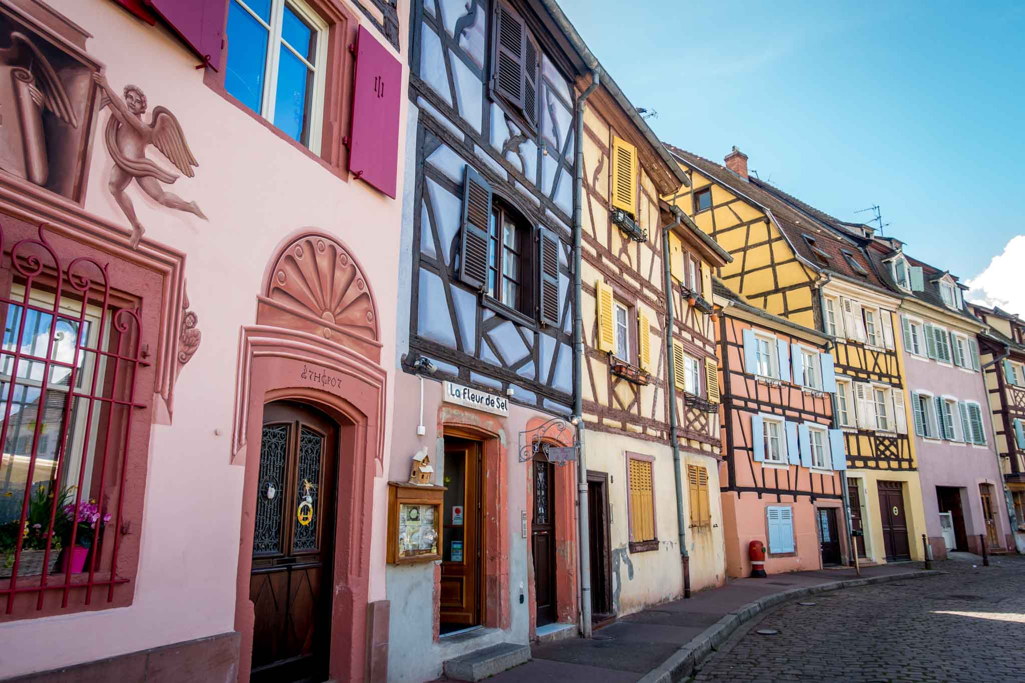 Row of half-timbered buildings painted pink, purple, and yellow