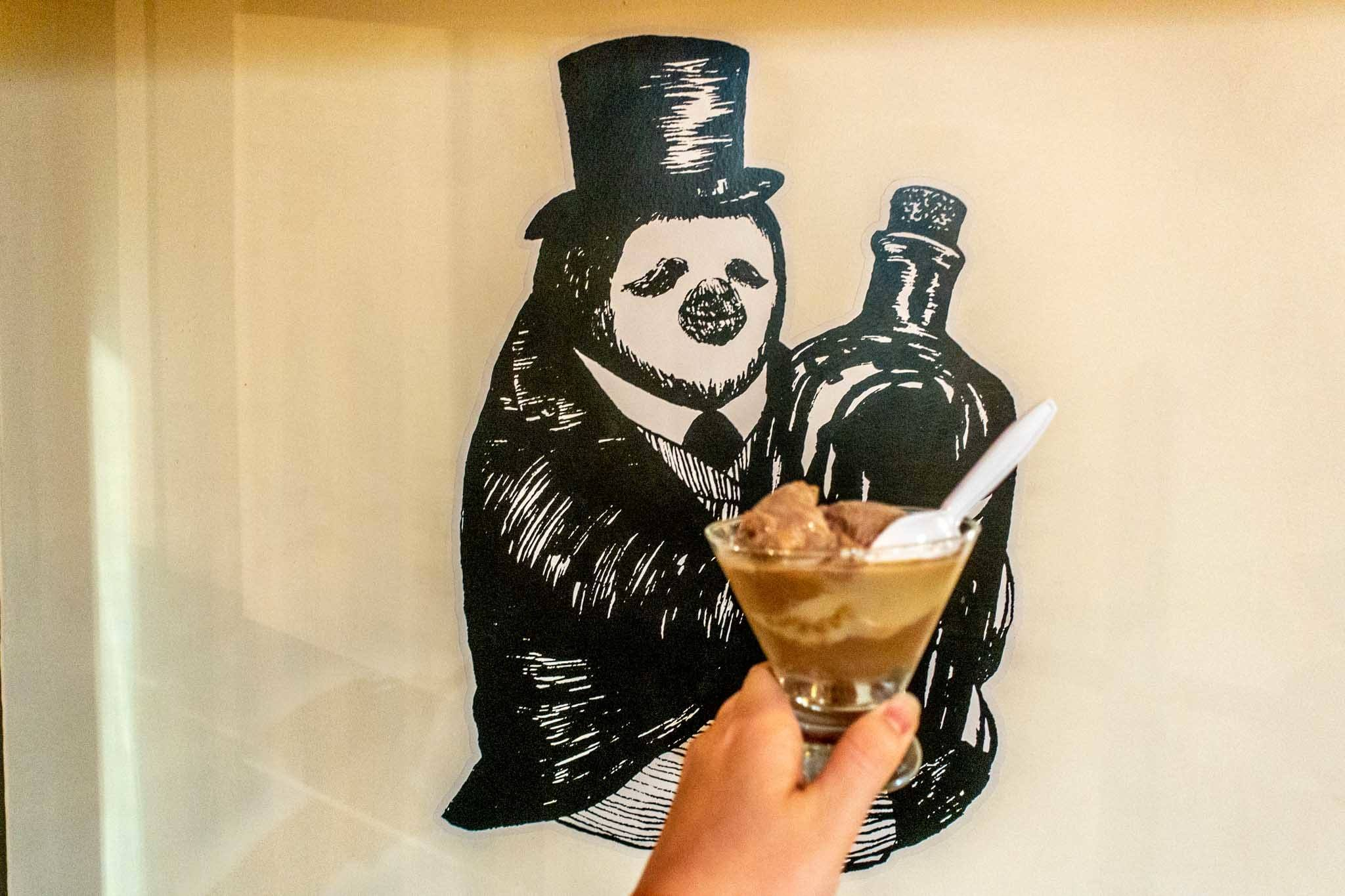 Dish of ice cream in front of a drawing of a penguin holding a bottle
