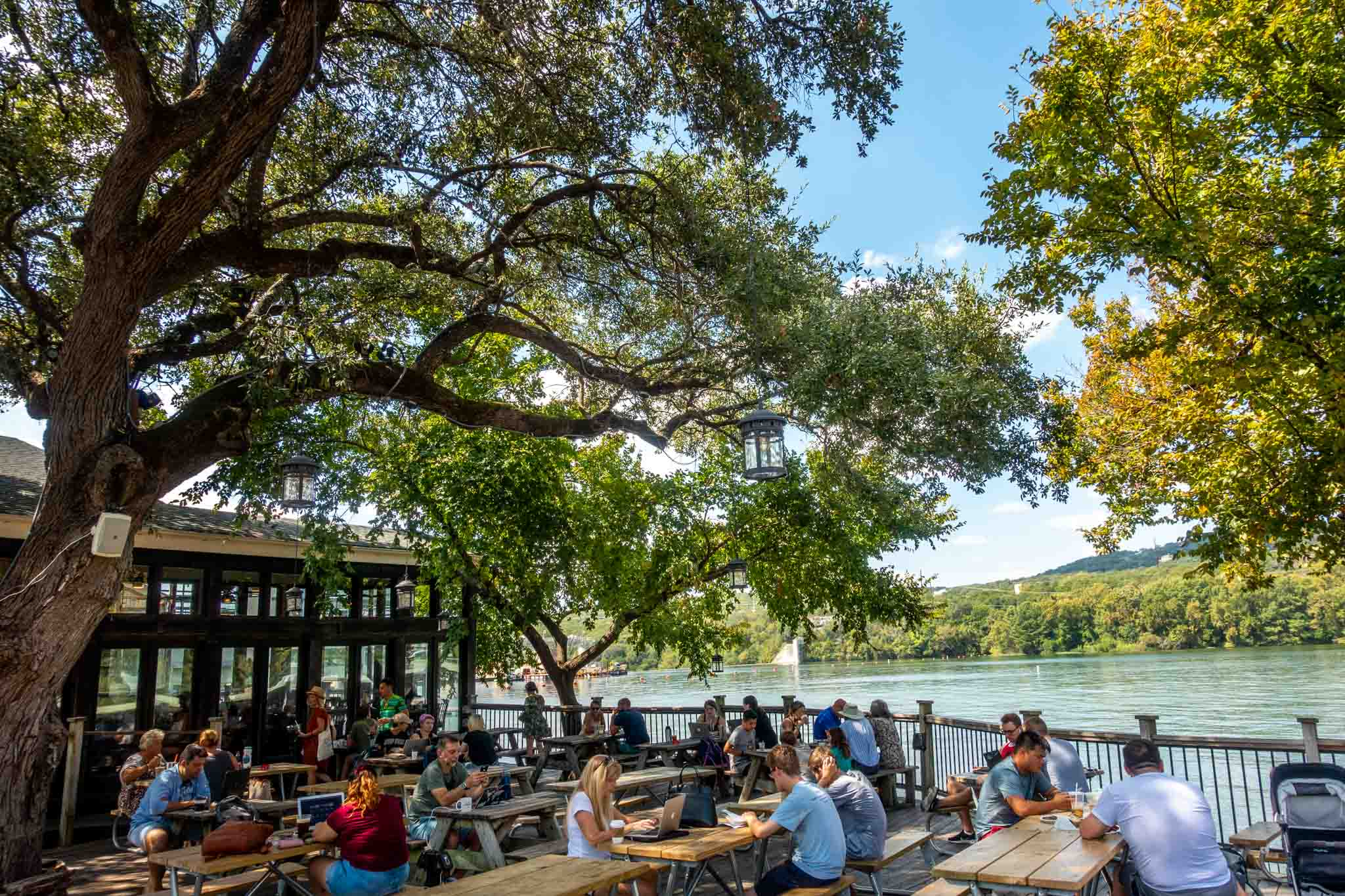 People sitting at picnic tables on a patio by Lake Austin