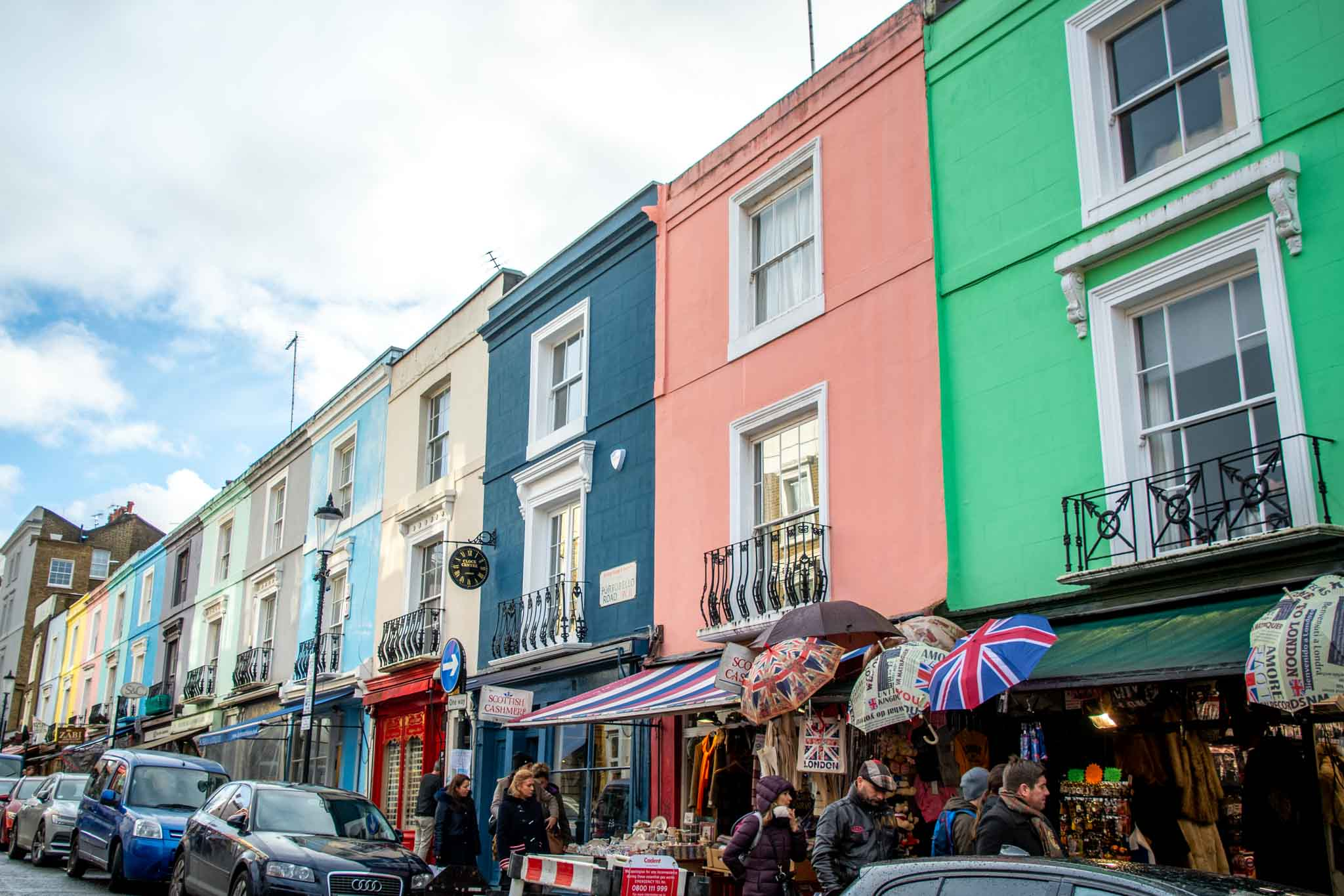 People walking by a row of colorful buildings on Portobello Road in Notting Hill