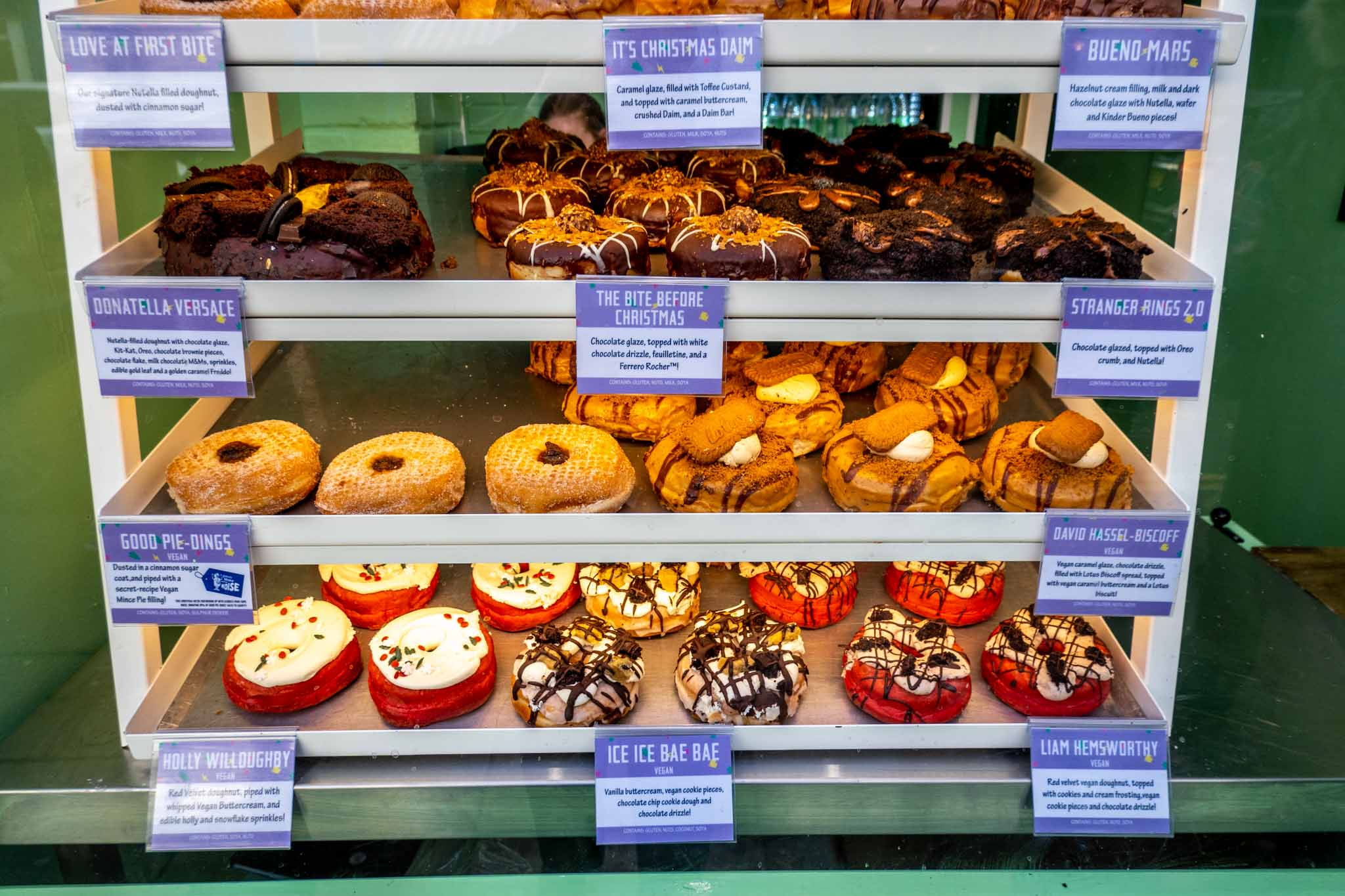 Shelves displaying decadent donuts with unusual names and flavors