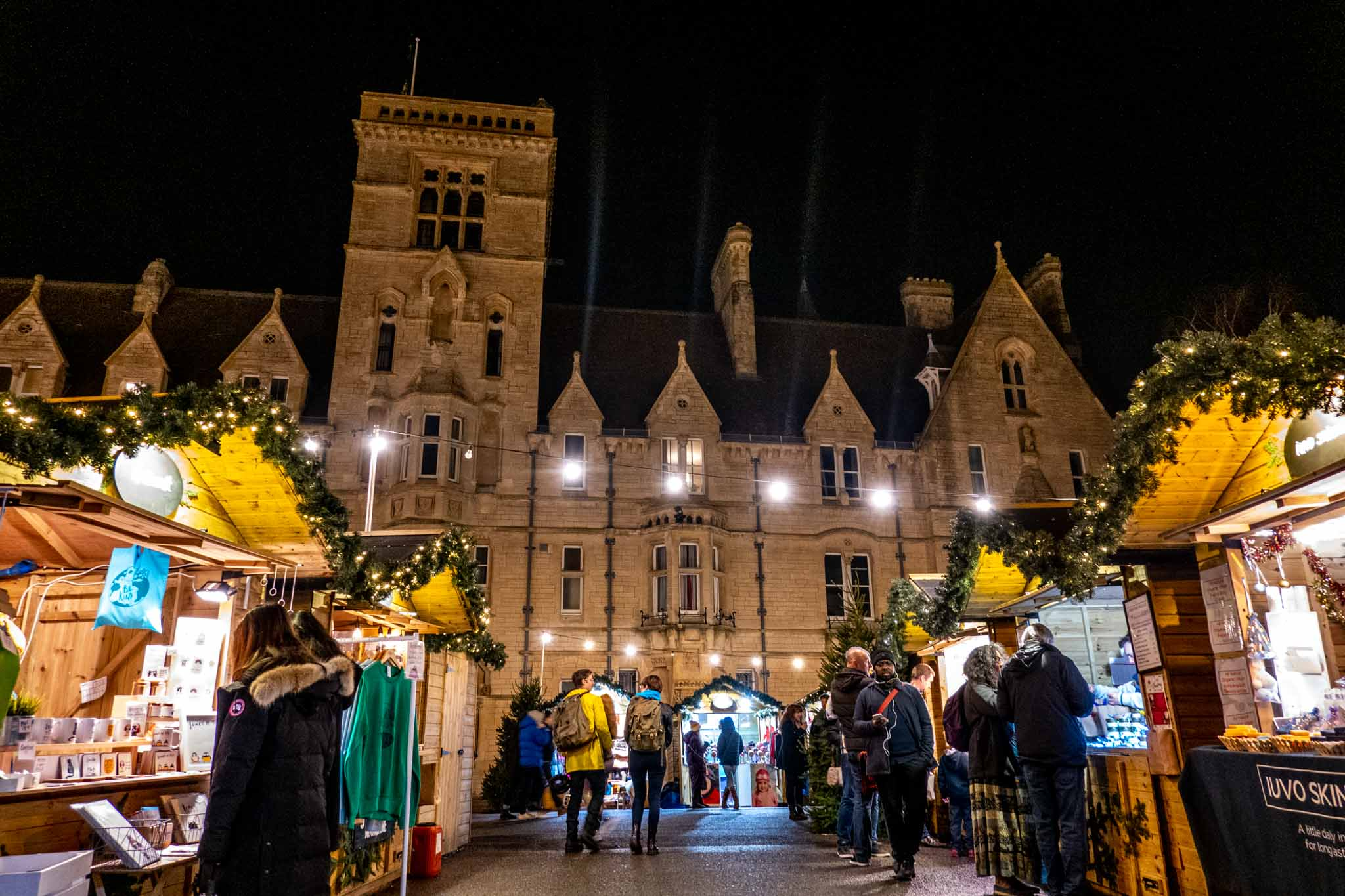 People shopping at the Oxford Christmas market with Balliol College buildings