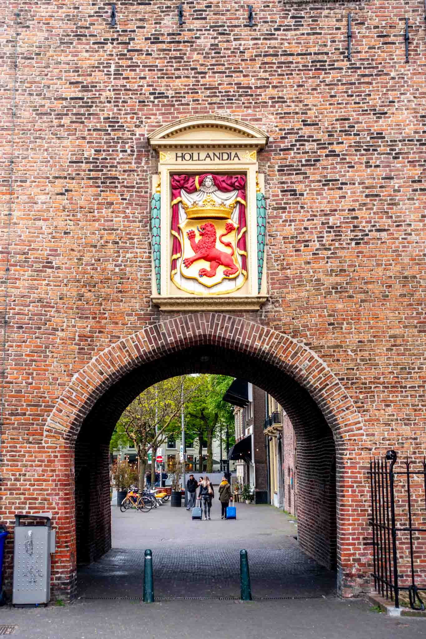 "Coat of arms and sign for ""Hollandia"" hanging over a brick city gate"