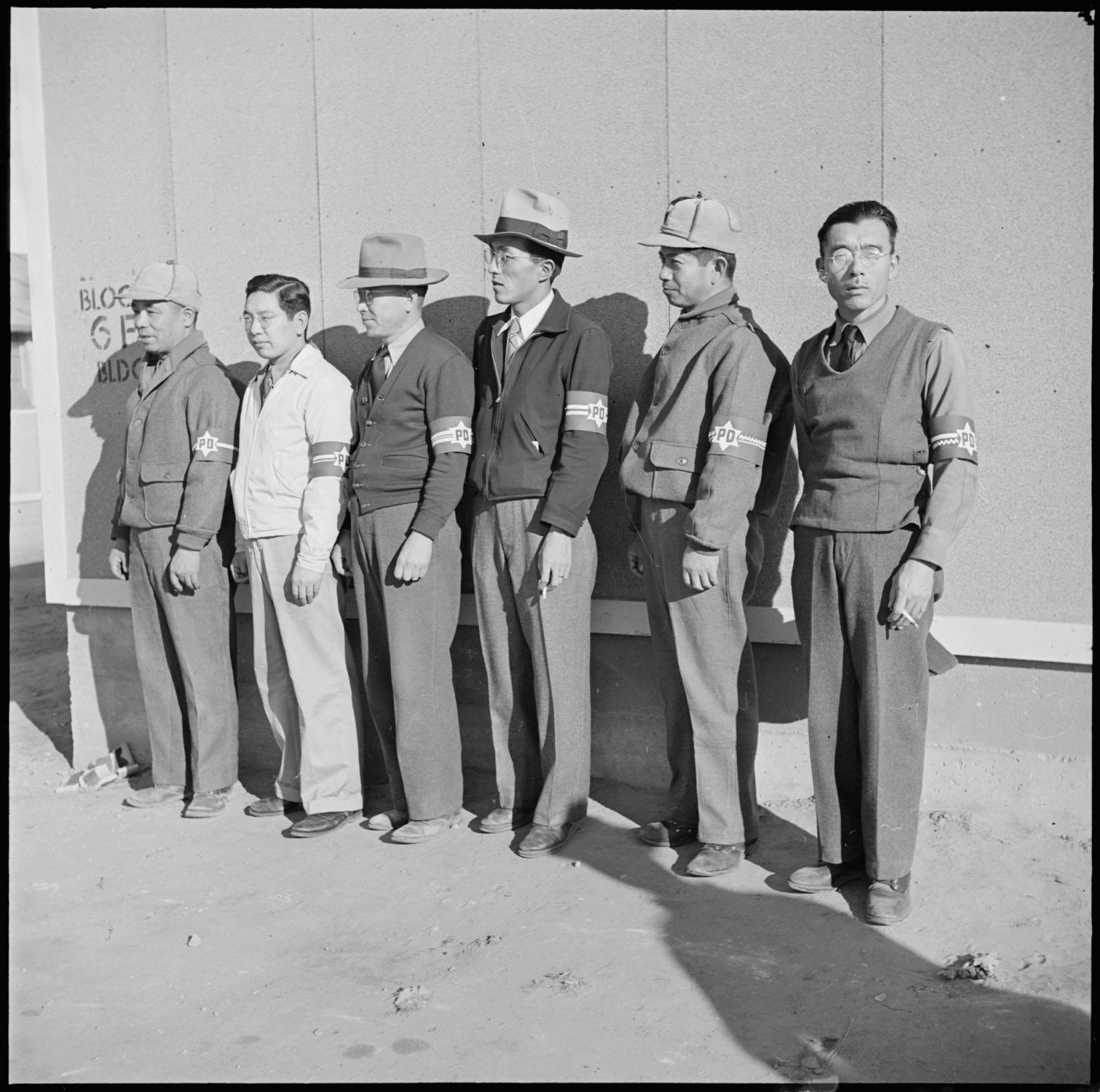 Japanese interment camp detainees wearing identification arm bands