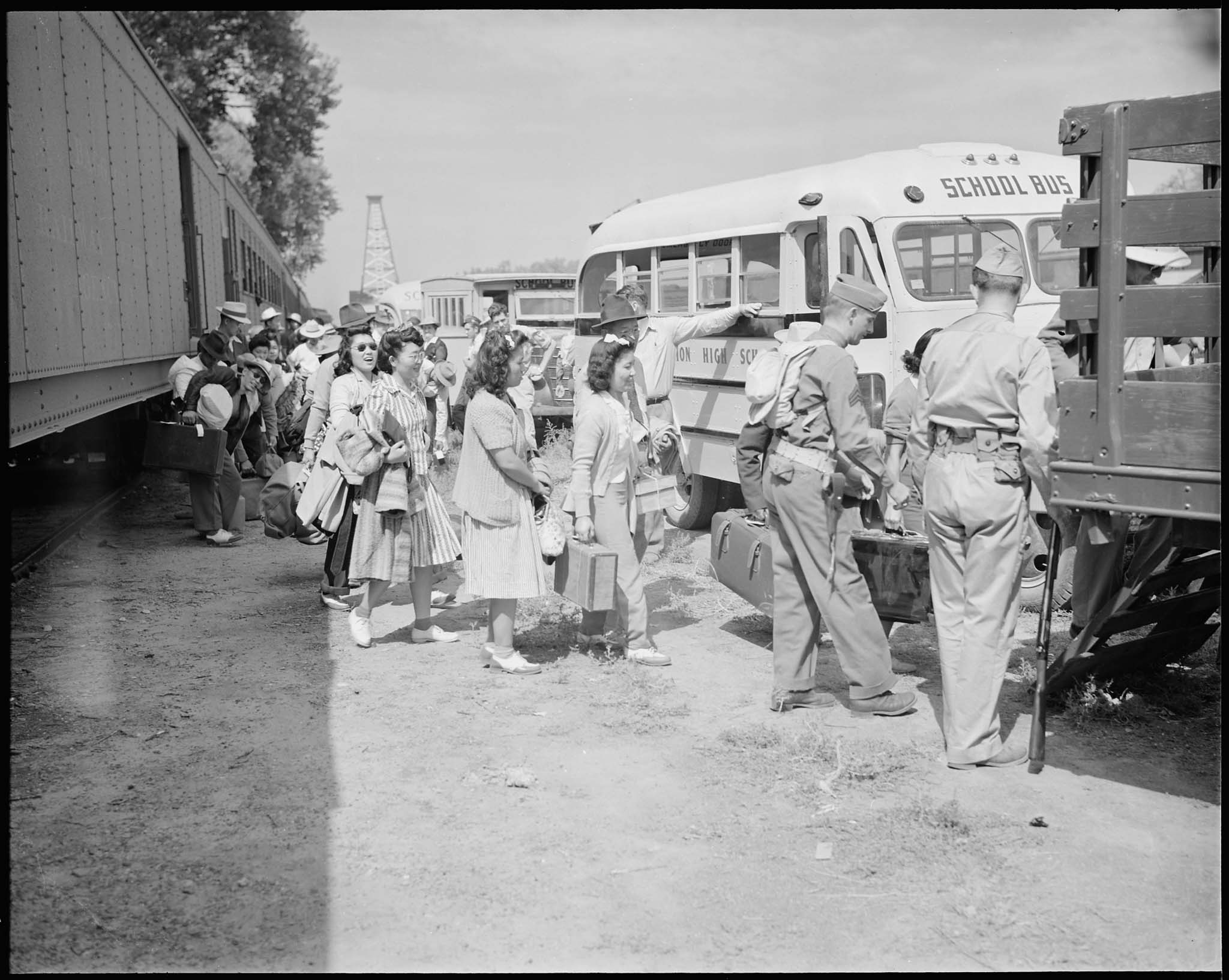 Japanese Americans leaving trains and boarding trucks and buses to the Granada Relocation Center