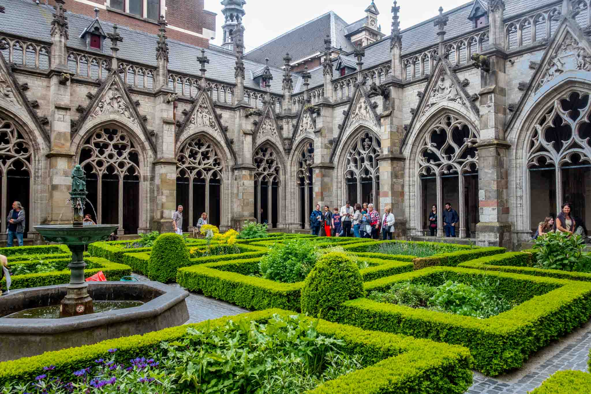 People in a garden surrounded by stone cloister building