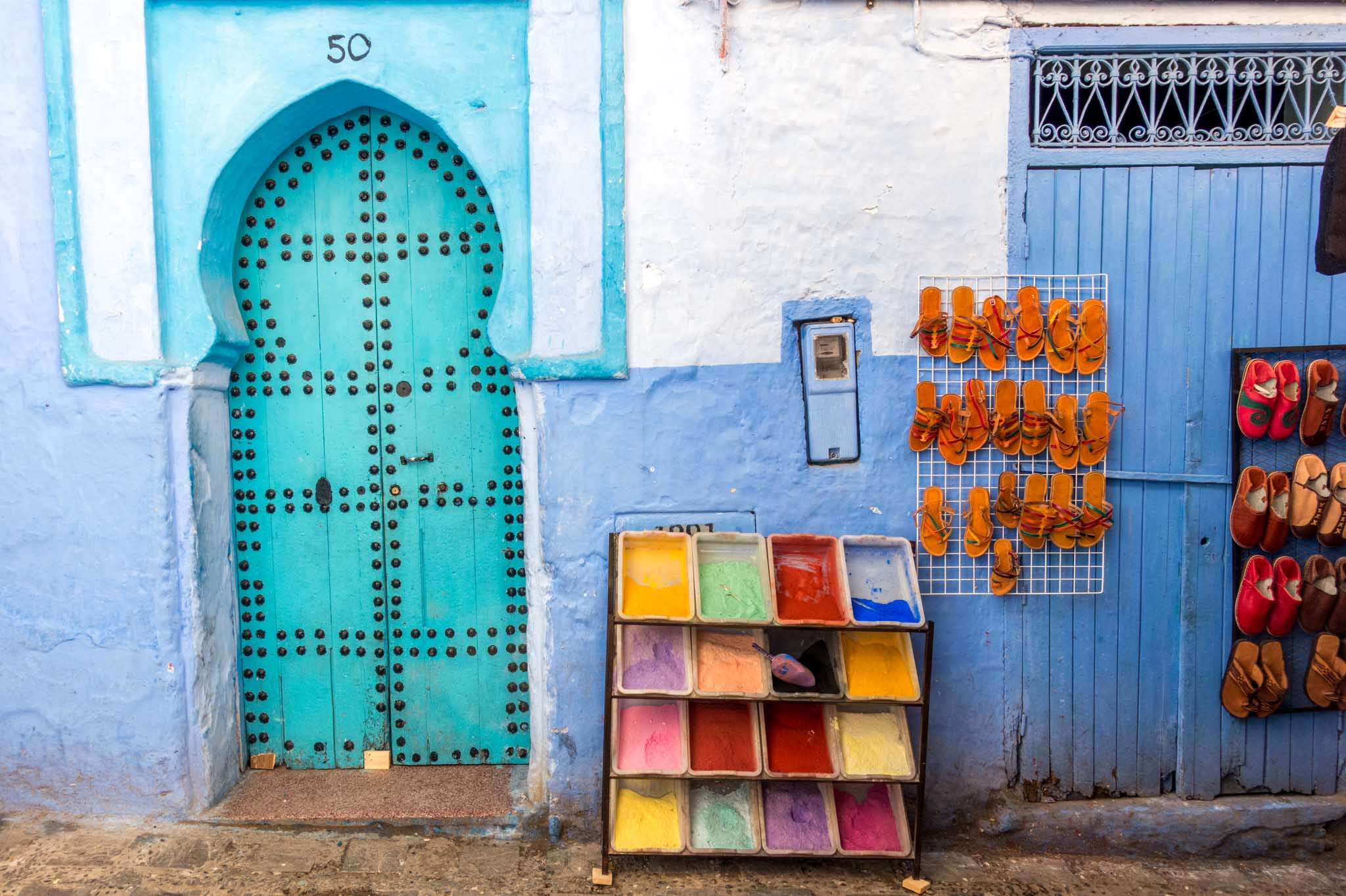 Multi-colored pigments and sandals for sale next to a turquoise door
