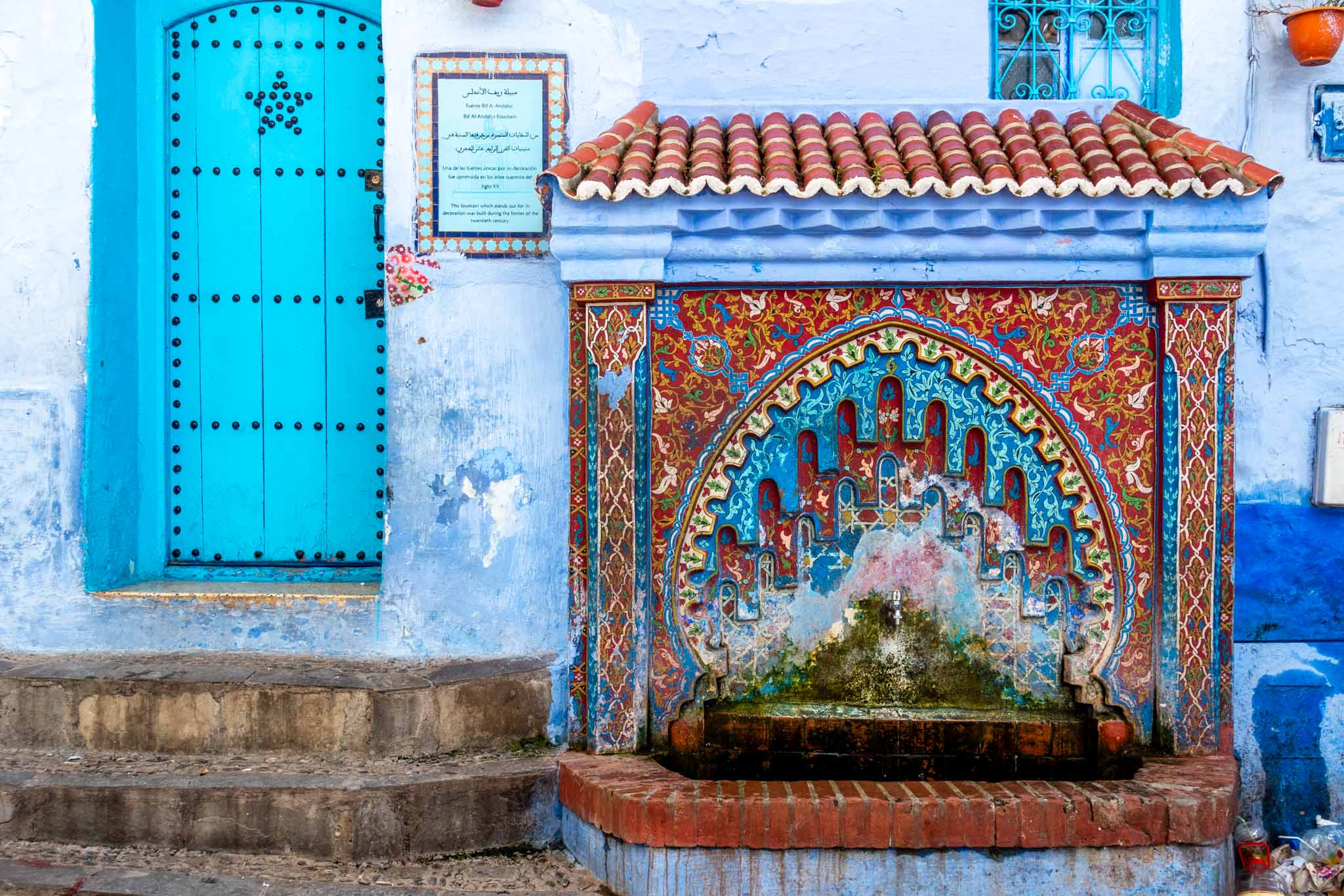 Red and blue decorated fountain next to a turquoise door