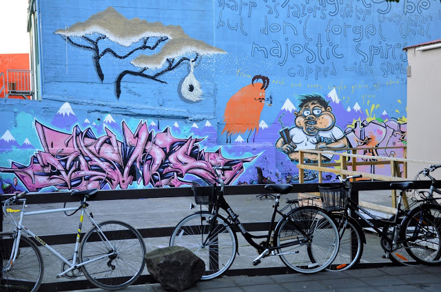 Purple and blue street art mural behind a row of bicycles