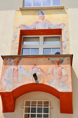 Pastel mural of people painted on yellow wall