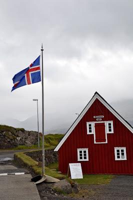 Red building and Iceland flag in Djupivogur